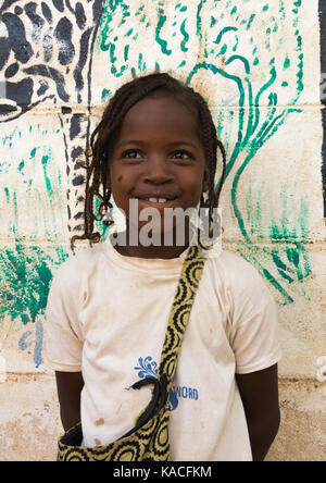 Nyangatom tribe girl in front of a school wall depicting animals, Kangate, Omo Valley, Ethiopia - Stock Photo