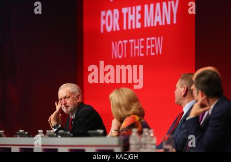 Labour Party leader Jeremy Corbyn waves to someone whilest on stage during the second day of the Labour Party Conference - Stock Photo
