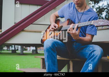 A young man plays a guitar. - Stock Photo