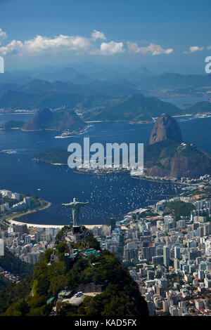 Christ the Redeemer statue atop Corcovado, and Sugarloaf Mountain, Rio de Janeiro, Brazil, South America - aerial - Stock Photo
