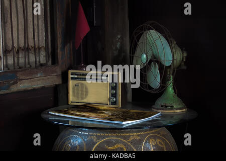 Still Life with household appliances. Still life with old radio and electric fan, magazine and banner with wood - Stock Photo