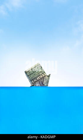 Drowning in debt. Upside down origami cash home sinking in water. - Stock Photo