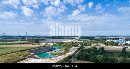 Limestone break from the distance, wind turbines in the background, dramatic sky, aerial photo with the drone - Stock Photo