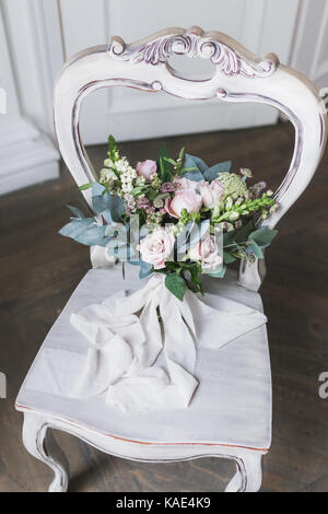 Bridal bouquet on vintage white wooden chair - Stock Photo