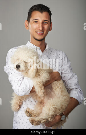 Hispanic young smiling man with poodle dog - Stock Photo
