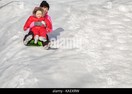 Happy mother and her daughter enjoying a sledge ride down the hills, winter games and fun.  Family holiday and togetherness. - Stock Photo