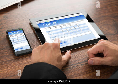 Close-up Of A Businessman Filling Survey Form Online On Digital Tablet And Cellphone - Stock Photo
