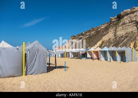 Seasonal canvas tents on the beach. Nazare, Estremadura Region, Portugal - Stock Photo