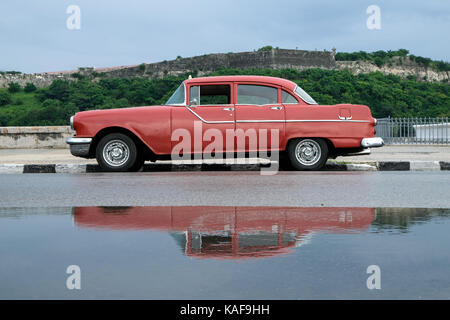 A vintage car is reflected in a pool of rain water on the Malecón in Havana, Cuba, after a large rain storm. - Stock Photo