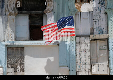 A United States flag flies outside a decrepit building in Centro Habana in Havana, Cuba. - Stock Photo