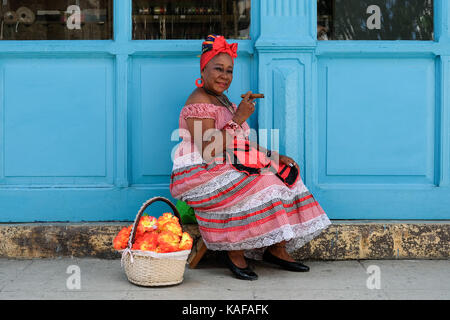 A colourfully dressed Cuban woman in traditional clothing sits on the streets of Habana Vieja in Havana, Cuba. - Stock Photo