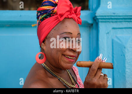 A colourfully dressed Cuban woman holds a cigar as she sits on the side of the street in Habana Vieja in Havana, - Stock Photo