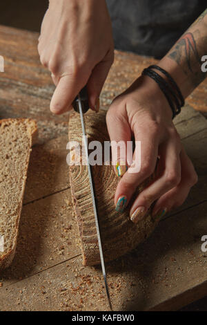 Female hands cut freshly baked bread - Stock Photo