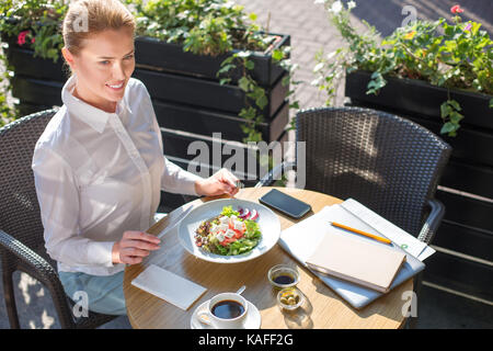Smiling woman being about to eat Greek salad - Stock Photo