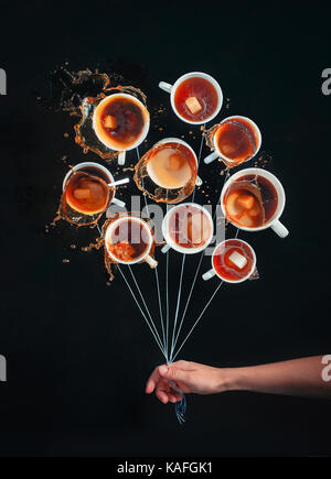 Bouquet of white coffee cups with splashes, looking like a bunch of balloons on a black background. Dynamic still - Stock Photo