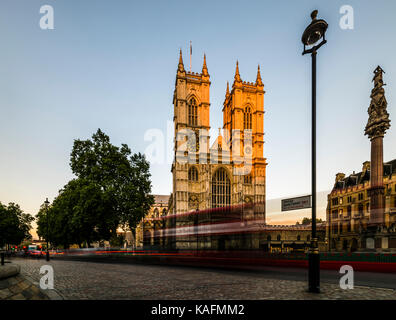 Red London buses in front of Westminster Abbey at dusk, London, UK - Stock Photo