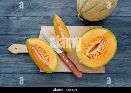 Fresh cantaloupe cut into pieces on wooden table. - Stock Photo