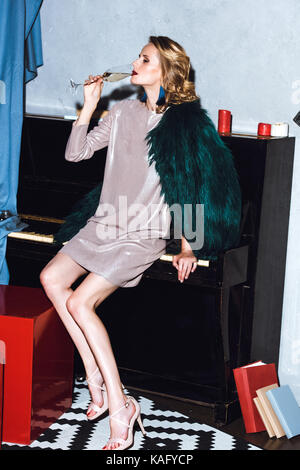 young woman sitting on piano - Stock Photo