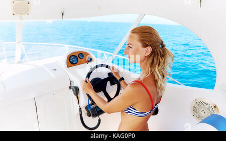 Young blond woman in bikini steering the sailing boat - Stock Photo