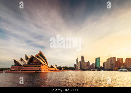 Sydney, Australia - November 10, 2015:  Opera House with Sydney city skyline at sunset. View from ferry approaching - Stock Photo
