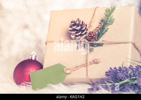 Brown paper craft warped on present box with label tag decorate with pine cone and green leaf christmas ball at - Stock Photo