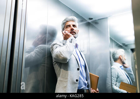 Mature businessman with smartphone in the elevator. - Stock Photo