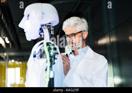 Businessman or a scientist with a robot. - Stock Photo
