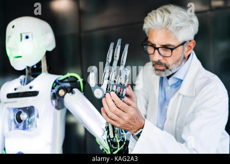 Mature businessman or scientist with a robot. - Stock Photo