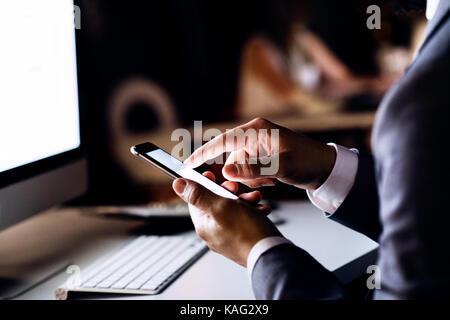 Unrecognizable businessman in the office at night. - Stock Photo