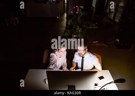 Businesspeople in the office at night working late. - Stock Photo