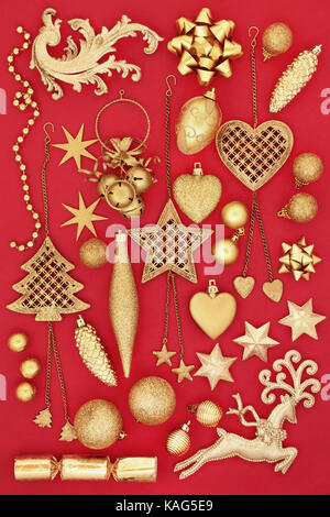 Gold symbols and bauble decorations of christmas on red background. - Stock Photo