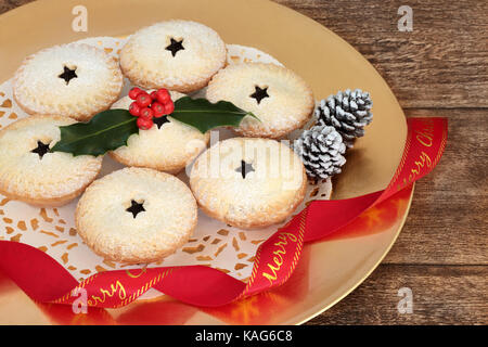 Christmas mince pies with holly and red ribbon on a gold plate on oak wood background. - Stock Photo