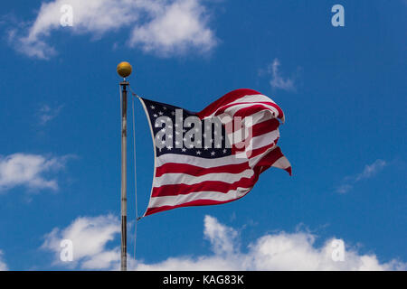American flag against blue sky. - Stock Photo