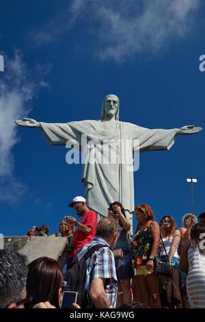 Tourists and Giant statue of Christ the Redeemer atop Corcovado, Rio de Janeiro, Brazil, South America - Stock Photo