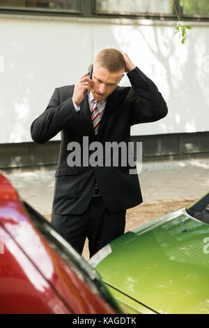 Male Driver Making Phone Calls After Traffic Accident - Stock Photo