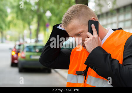 Young Male Driver Making Phone Calls With A Broken Down Cars On Road - Stock Photo