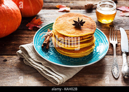 Pumpkin pancakes served with honey. Autumn food concept - Stock Photo