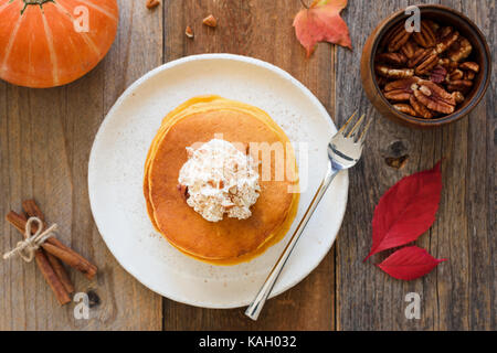 Pumpkin pancakes with whipped cream and cinnamon on wooden table. Top view, horizontal - Stock Photo