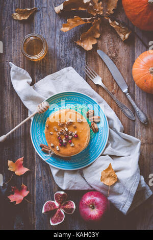 Pumkin pancakes on a blue plate on wooden background served with pecan nuts and honey. Autumn food still life - Stock Photo