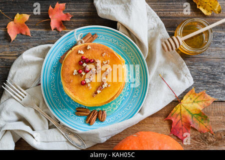 Pumpkin pancakes with honey, pecan nuts and berries on a plate. Table top view. Homemade pumpkin pancakes autumn - Stock Photo