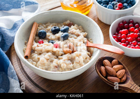 Oatmeal porridge with blueberries, almonds and currants in bowl. Healthy breakfast, dieting, balanced meal concept - Stock Photo