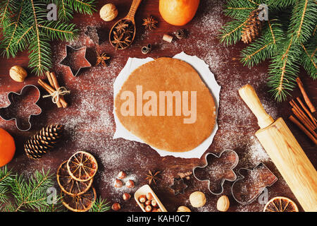 Gingerbread cookie dough rolled out on the table with Christmas and New Year decorations. Cookie cutters, fir tree, - Stock Photo