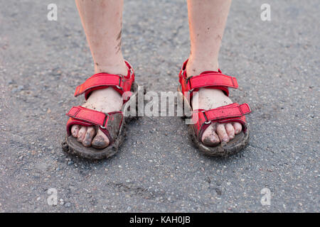 closeup of child's dirty feet in red sandals on asphalt - Stock Photo