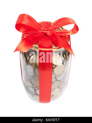 Coins in the jar with red ribbon on white background - Stock Photo