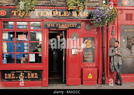 Man stands outside The Temple Bar in Dublin, Ireland. - Stock Photo