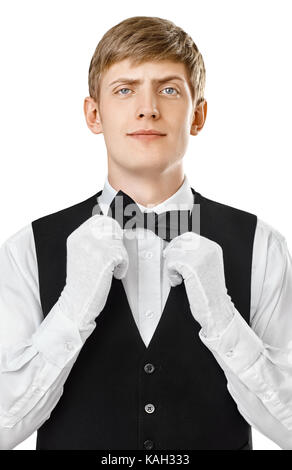 Portrait of young handsome waiter fixing his bow tie on a suit isolated on white background - Stock Photo