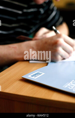 A man fills in an application form for the police service. Newport, South Wales. 20.03.2006. - Stock Photo