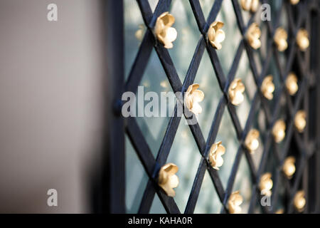 old metal lattice window in the wall - Stock Photo