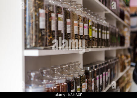 many glass jars with tea on store shelves - Stock Photo