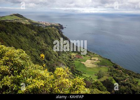 View from Miradouro da Faja do Conde to the east coast, in the back left the capital of Santa Cruz, island Flores, - Stock Photo